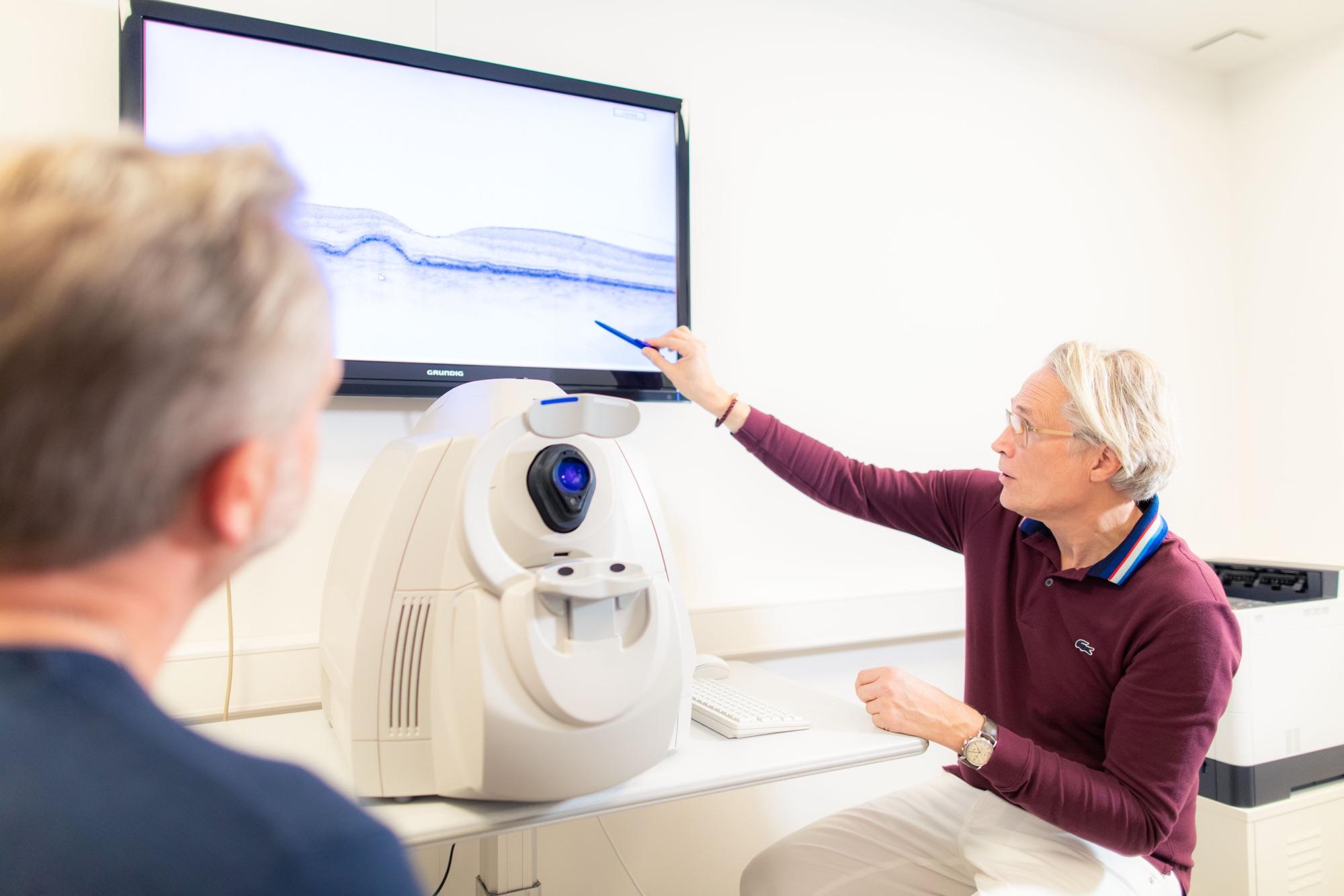 Augenarzt Thomas Müller erläutert einem Patienten einen OCT-Befund.
