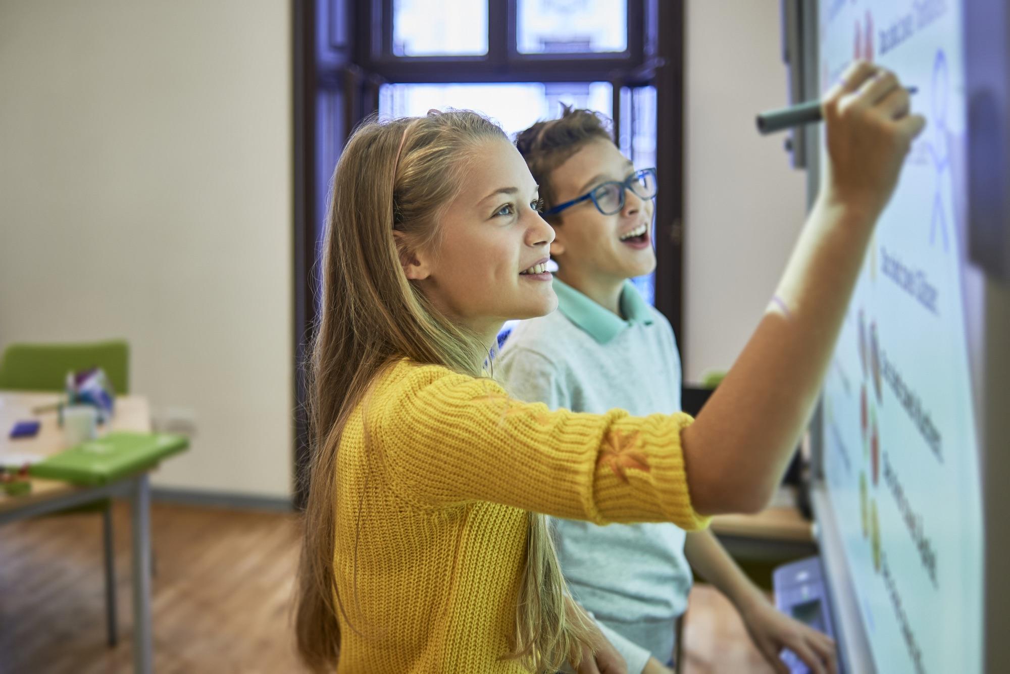 Mädchen mit gelbem Pullover schreibt an die Tafel, neben ihr steht ein Junge mit einer Brille.